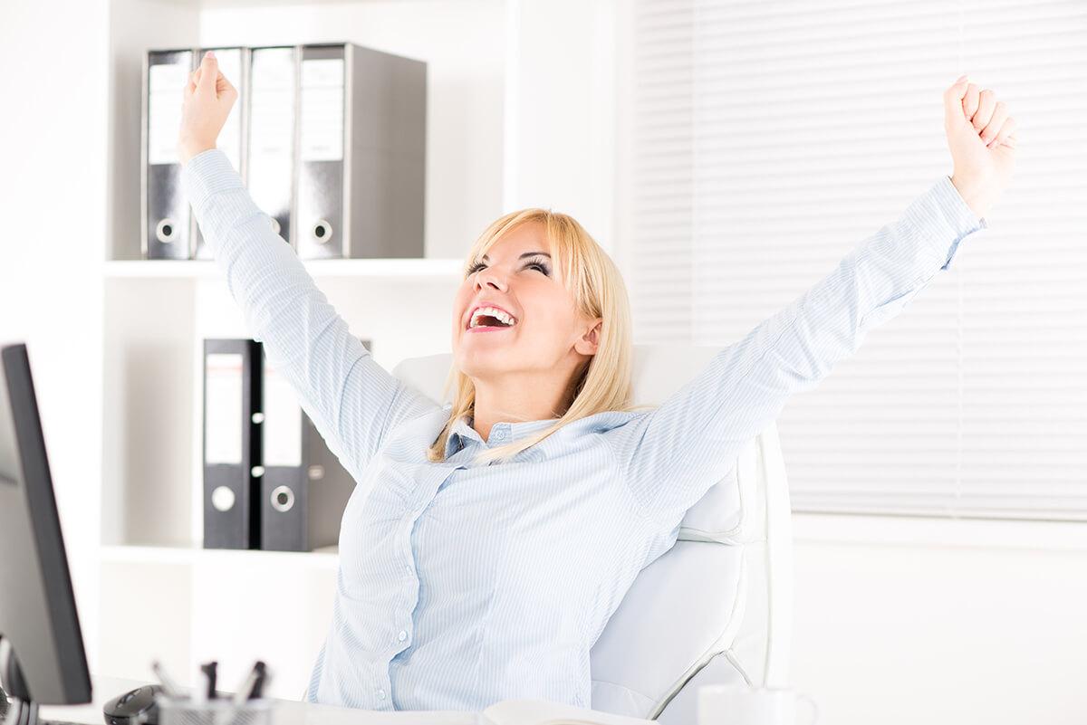 mulher feliz no trabalho com os braço para cima