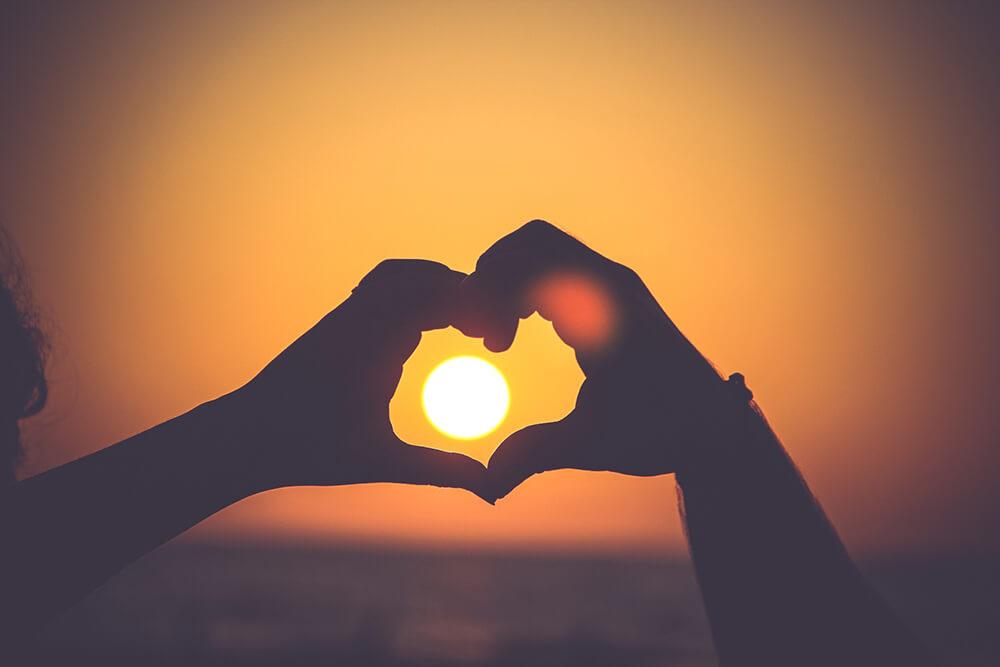 por dos sol ao fundo e mãos no formato de coração