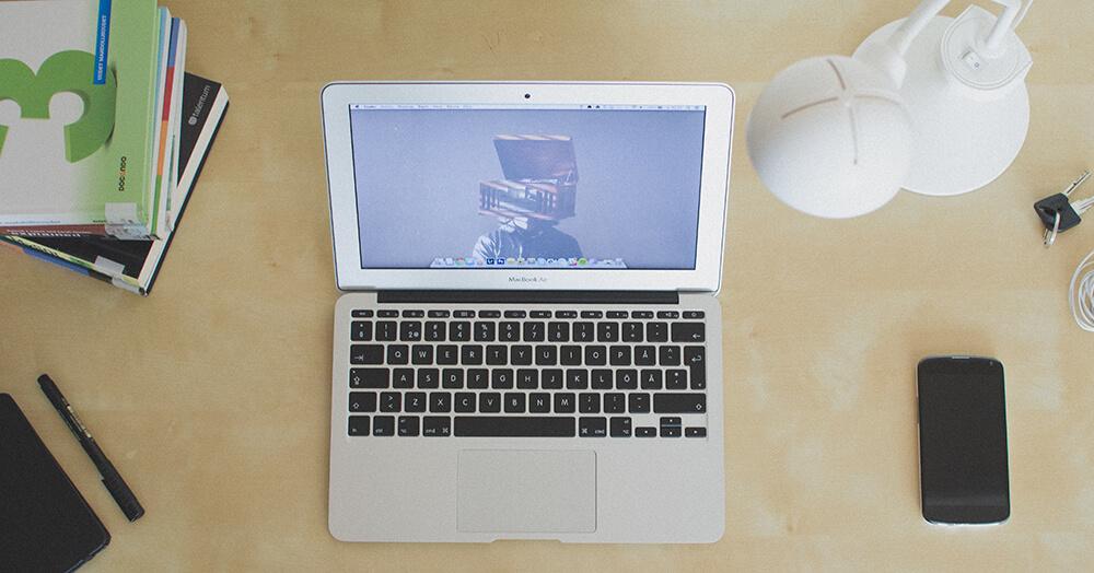 mesa de trabalho com notebook, livros, celular
