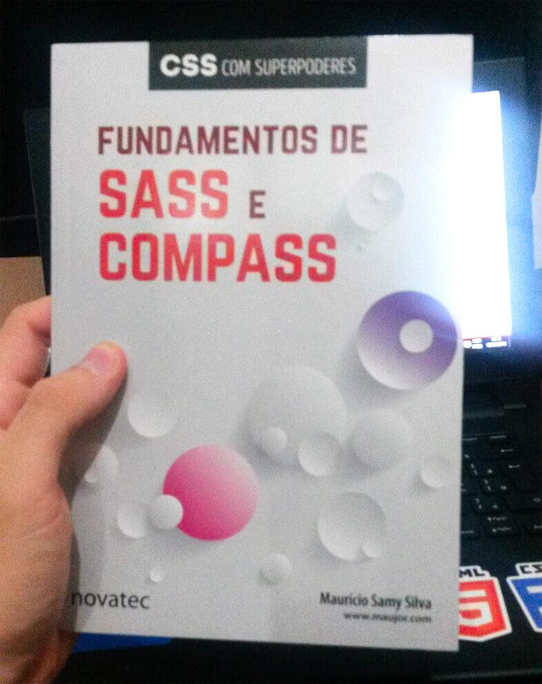 Foto segurando o Livro Fundamentos de SASS e COMPASS