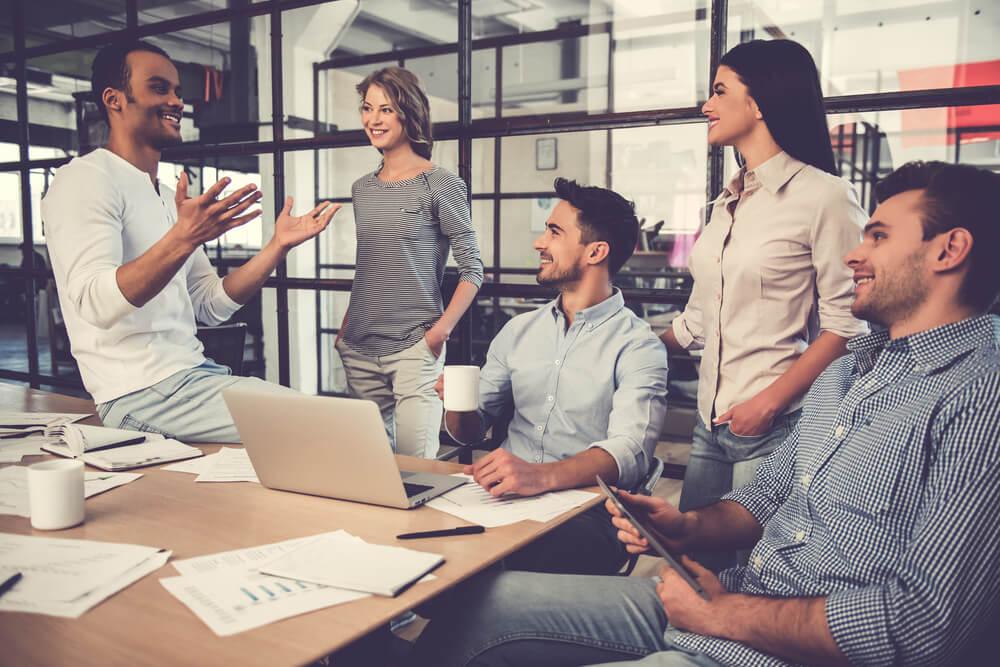 Quero ser Designer! Vou passar fome? - Foto de Pessoas trabalhando, conversando e sorrindo em uma reunião no escritório Por George Rudy /Shutterstock