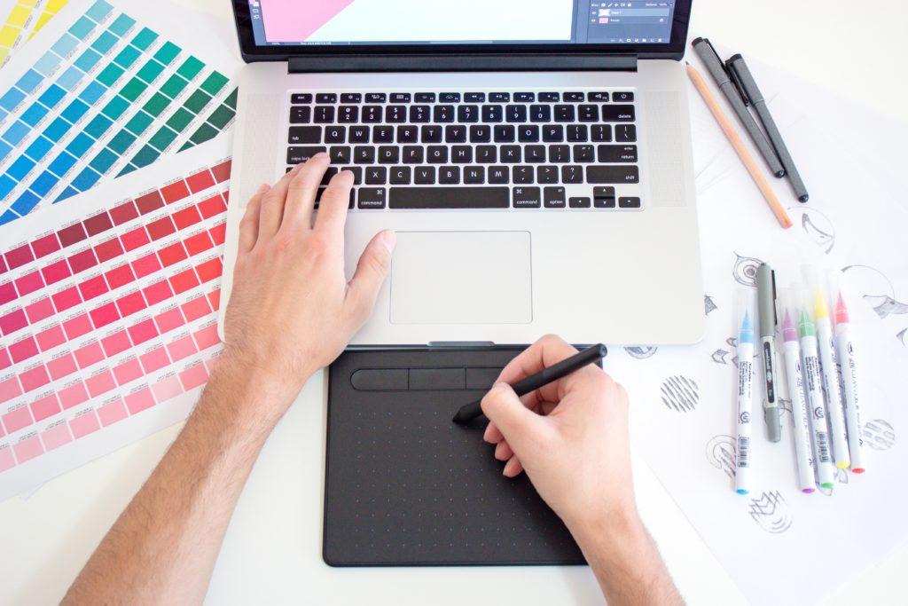 Designer gráfico trabalhando em um laptop Macbook usando um trackpad, tabelas de cores e marcadores